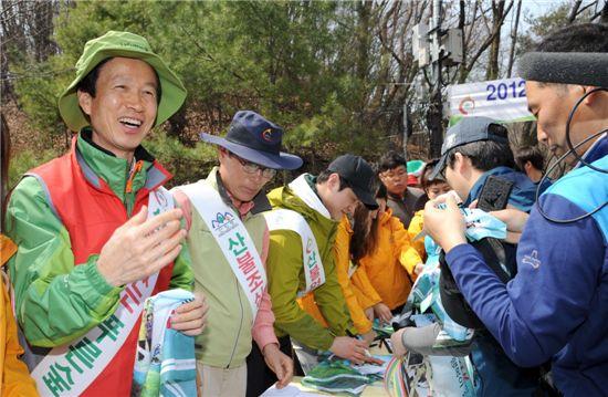 등산객들에게 산불방지를 강조하며 기념품을 나눠주고 있는 이돈구(맨 왼쪽) 산림청장