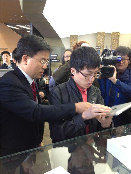 ▲표현명 KT 사장이 뉴 아이패드 1호 개통자인 임준홍씨와 직접 뉴아이패드 박스를 개봉하고 개통을 돕고 있다.