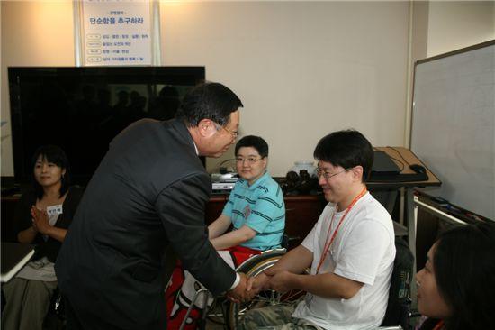 장애인 사우 입사식에서 도상철 NS홈쇼핑 대표가 사원과 악수를 나누고 있다.