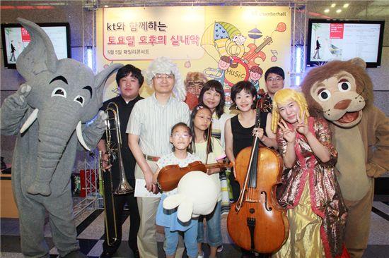 KT는 어린이 날을 맞이해 지난 5일 서울 양천구 목동에 위치한 KT체임버홀에서 '패밀리 클래식 콘서트'를 열었다. 사진은 콘서트를 관람한 어린이들(과 가족들)이 '동물의 사육제'에 등장하는 동물인 사자, 코끼리 및 공연 연주자들과 함께 포즈를 취하고 있는 모습.