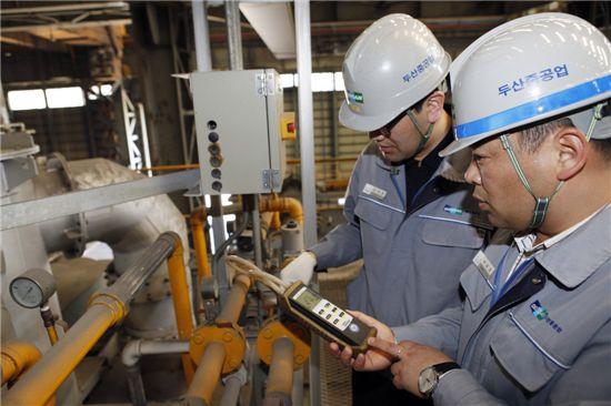 ▲경남 창원에 위치한 두산중공업 단조공장에서 온실가스 담당자들이 탄소배출 계측기 수치를 확인하고 관련 설비를 점검하고 있다.