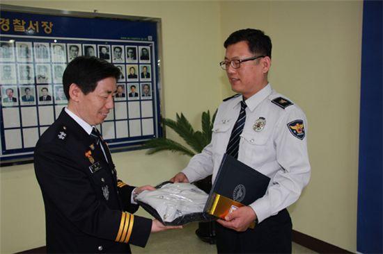 아산경찰서 장성수(오른쪽) 경사가 정용선 충남지방경찰청장으로부터 새 경찰복을 받고 있다.