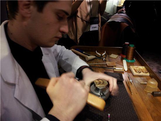 구찌의 장인이 뱀부 시계를 만들기 위해 대나무 베젤을 그을리고 있다.