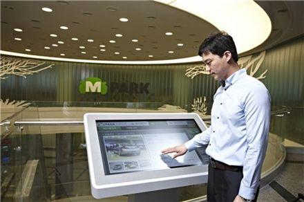 2일 인천 엠파크에서 한 방문객이 키오스크를 이용해 중고차 정보를 검색하고 있다.