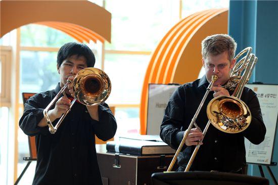혜광학교 원희승(19)군과 베를린 필하모닉 트롬보니스트 토마스레옌데커가 나란히 서서 연주 중이다.