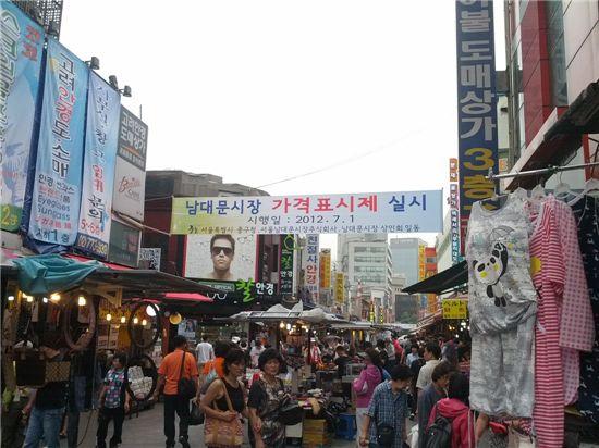 ▲서울 중구는 1일부터 서울 남대문시장 일대에서 '가격표시제'를 실시한다며 플래카드를 붙였다. 이에 따라 40개 상가 6100개 점포 중 모든 소매점포는 개별 상품에 '판매가○○원'으로 금액을 표시해야 하지만 실제 이날 가격라벨을 붙인 점포는 거의 없었으며 '탁상행정'에 불과해 실효성이 떨어진다는 볼멘 목소리가 높았다.