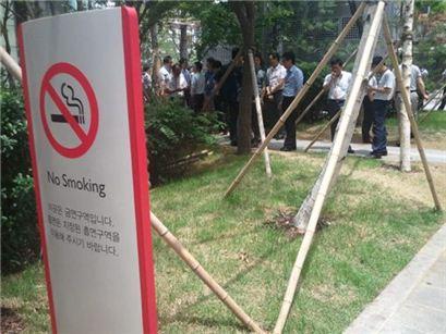 ▲ 파인에비뉴 빌딩 인근에 금연표지판이 설치돼 있다. 하지만 이 표지판 5m 전방에 흡연장소가 마련돼 있어 혼란을 가중시키고 있다. 사진은 표지판 앞 흡연장소에서 흡연자들이 모여 있는 모습. 표지판과 흡연공간은 중구청 요청으로 빌딩 측에서 마련했다.