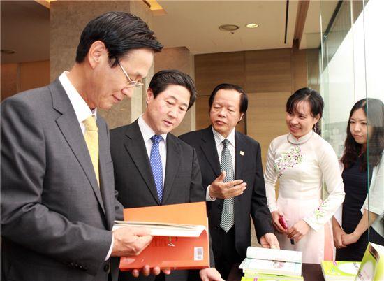 민병덕 KB국민은행장(왼쪽), 유기준 국회의원(왼쪽 두번째), 촨 총 돤 주한 베트남 대사(왼쪽세번째)가 함께 한국어교재를 보고 있다