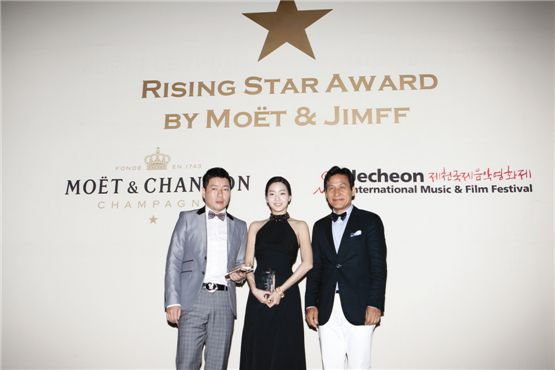 """Director Lee Sang-woo of 2012 film """"Barbie"""" (left), actress Kim Go-eun of 2012 film """"Eungyo"""" (center) and veteran actor Ahn Sung-ki pose with trophies the Moet & Chandon Rising Star Awards co-hosted by Jecheon International Music and Film Festival and Moet Chandon in Jecheon, South Korea on August 10, 2012. [Lee Jin-hyuk/10Asia]"""