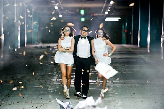 "PSY walks out from a parking lot with his female backdancers in the music video for ""Gangnam Style,"" the title song of his sixth studio album ""Six Rules, Pt. 1"" released on July 15, 2012. [YG Entertainment]"