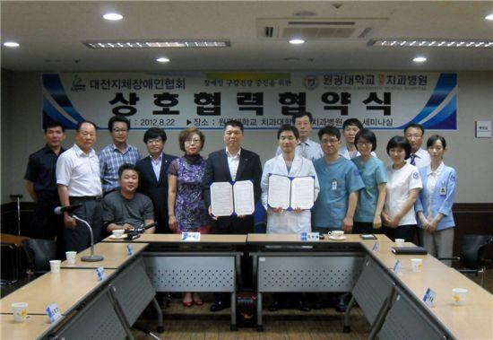 대전지체장애인협회와 원광대 치과대가 협약을 맺고 양쪽 관계자들이 기념사진을 찍고 있다.