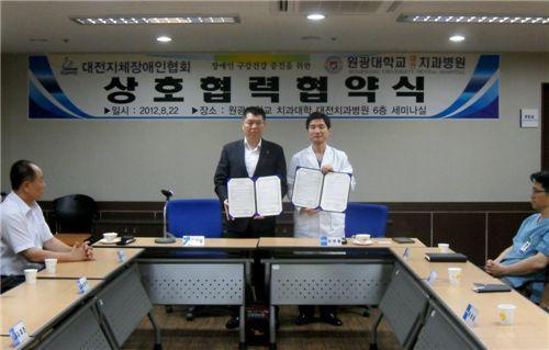 윤석연(왼쪽) 대전시지체장애인협회장과 김상철 원광대 치과대 대전치과병원장이 협약서를 펼쳐보이고 있다.