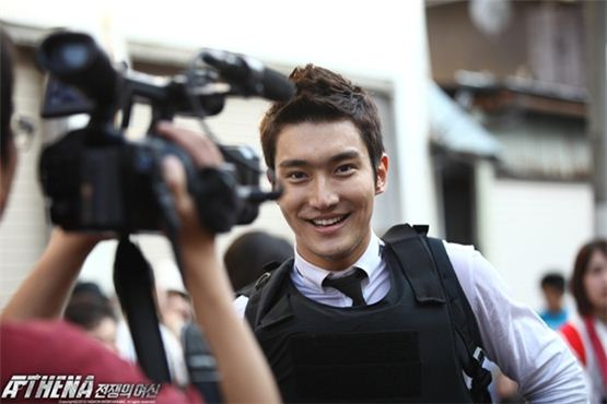 """Singer and actor Choi Siwon smiles in front of the camera on the set of SBS' action crama """"ATHENA,"""" aired between December 13, 2010 and February 21, 2011. [SBS]"""