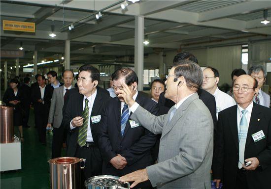 최진민 귀뚜라미 명예회장(오른쪽 두번째)이 보일러업계 관계자들에게 신제품에 대해 설명하고 있다.