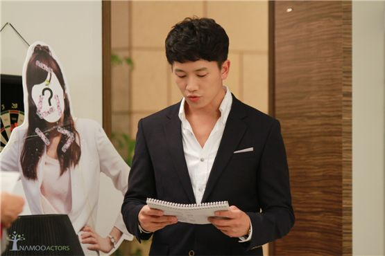 "Actor Ji Sung reads a scenario on the set of SBS' drama ""Protect the Boss,"" which aired between August 3 and September 29, 2011. [Namoo Actors]"