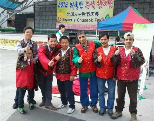 '이주외국인 추석한마당' 행사에 참가한 외국인근로자들과 행사를 마련한 김봉구(맨 왼쪽) 대전이주외국인종합복지관장이 포즈를 잡았다.