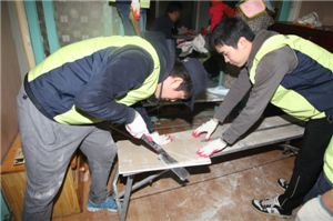 사랑의 집고치기 봉사활동에 참여한 삼양그룹 임직원들이 벽면공사작업을 펼치고 있다.