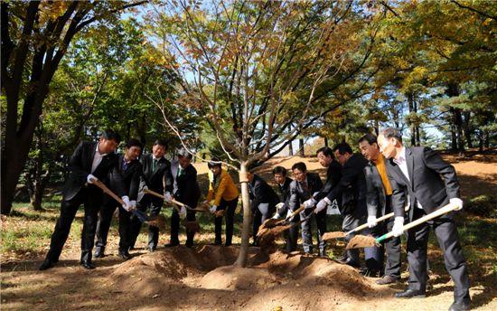 산림비전 공유 심포지엄 참석 내빈들이 기념나무를 심고 있다.