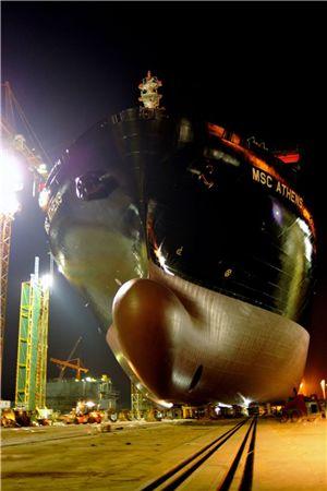 ▲성동조선해양이 22일 새벽 육상에서 건조한 8800TEU급 컨테이너선을 로드아웃하고 있다.