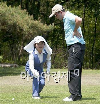 평양골프장의 북한 캐디가 한 외국인 골퍼의 플레이를 도와주고 있다.