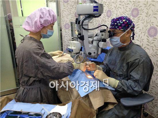 밝은광주안과 조철웅 대표원장이 백내장 질환으로 일상생활에 불편을 겪어온 환자의 눈에 인공수정체 삽입 시술하고 있다.