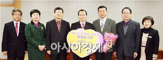 장흥전기 김장규 대표(오른쪽에서 세번째)가 에디슨 공부방 꾸미기 사업비 600만원을 기탁하고 이명흠 장흥군수(오른쪽에서 네번째)와 관계자들이 기념촬영을 하고 있다.