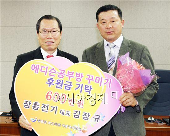 장흥전기 김장규 대표가 에디슨 공부방 꾸미기 사업비 600만원을 기탁하고 이명흠 장흥군수(왼쪽)와  기념촬영을 하고 있다.