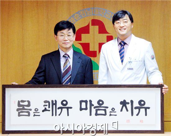 예가인 현곡 신명섭씨(왼쪽)가 화순전남대병원에 자신의 서예작품을 기증을  한 뒤 국훈 병원장과 기념촬영했다.