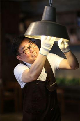 김재일 카페베네 총괄사장이 서울 압구정 갤러리아 매장을 방문해 전구를 빼는 모습. 과거 카페베네는 전국 매장의 조명을 평소보다 10% 줄어 운영하는 에너지 절약 캠페인을 진행한 바 있다.(사진제공=카페베네)