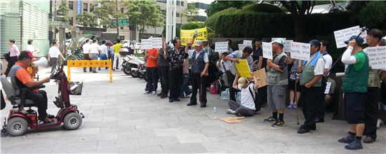▲26일 한 장애인 단체 소속 회원 40여명이 소공동 롯데호텔 앞에서 '도어맨 폭행 사건'과 관련해 롯데호텔이 고객 정보를 유출했다며 항의 집회를 벌이고 있다.