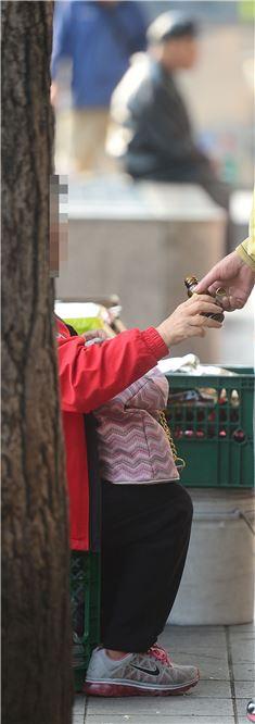 4일 서울 종로길 어느 작은 노점 옆 간이의자에 앉아있는 할머니에게 한 할아버지가 다가가 몇 마디를 주고받다가 자양강장제를 건네받고 있다. 백소아 기자 sharp2046@
