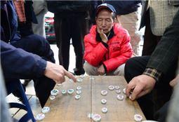 지난달 30일 서울 종로구 파고다공원 북문 근처에서 벌어진 장기판에 10여명이 몰렸다. 한 할아버지는 장기판 바로 옆에 쪼그려 앉아 장기를 구경하고 있다. 백소아 기자 sharp2046@