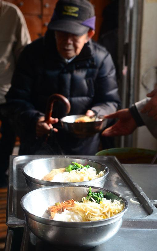 """지난 15일 서울 종로구 파고다 공원 북문에 위치한 원각사 무료급식소에서 어르신들이 배식을 받고 있다. 이곳의 점심메뉴는 매일 비빔밥이다. 그래도 식사를 마친 어르신들은 """"잘 먹었다""""는 인사를 잊지 않는다. 백소아 기자 sharp2046@"""