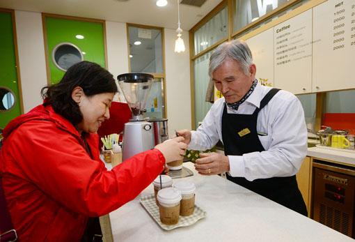 책마루 카페에서 일하는 이무일(69) 할아버지가 손님에게 커피를 건내주고 있다. 백소아 기자 sharp2036@