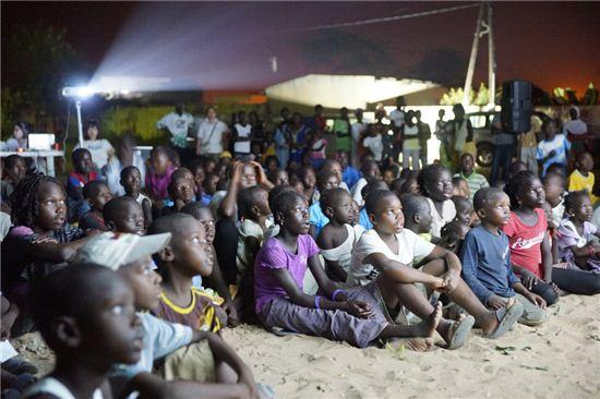 SK텔레콤과 메가박스가 세네갈 꺼르무사에 설치한 이동식 영화관에서 현지 어린이들이 영화를 관람하고 있다.