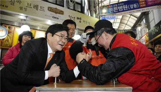 김기동 광진구청장(왼쪽)이 중곡제일시장 팔씨름 이벤트에 참석해 시장 상인과 팔씨름을 하고 있다.