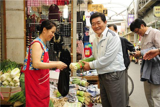 김기동 광진구청장(가운데)가 전통시장에서 장을 보고 있다.