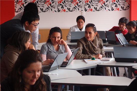 ▲한국 교육부의 '한국형 첨단교육서비스 해외진출 지원사업'을 수주한 LG CNS가 2011년 콜롬비아 우바떼 지역에 구축한 첨단교실. LG CNS 직원이 이 지역의 교사들에게 첨단교실 운영 방법을 교육하고 있다.