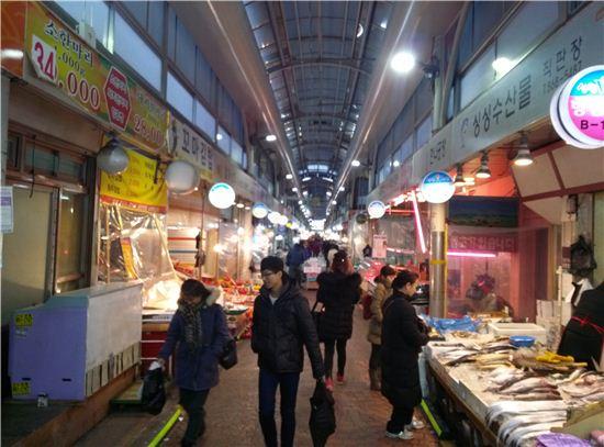 18일 신원시장을 찾은 소비자들이 좌판의 물건을 살피고 있다.