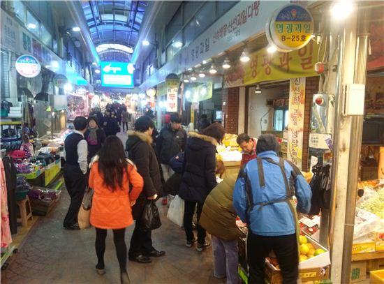 18일 신원시장을 찾은 소비자들이 한 과일점포 앞에서 물건을 살피고 있다.
