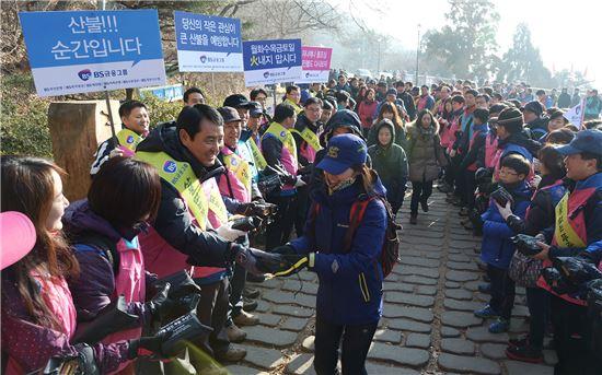 성세환 BS금융 회장(왼족에서 세번째)이 18일 금정산 등산로에서 산불예방 문구가 담긴 산행용품을 등산객들에게 나눠주고 있다.