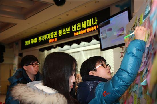 지난 18일 한국투자증권 본사 대강당에서 열린 '2014 제4회 청소년 비전 세미나' 행사에서 참여학생들이 'APPA(평화나눔공동체)-UN 빈곤퇴치 캠페인' 보드에 전세계 불우이웃에게 보내는 희망의 메시지를 작성하고 있다.