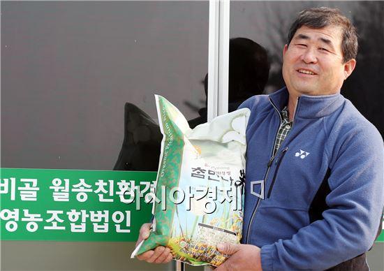 오관수 함평 나비골월송친환경영농조합법인 대표가 친환경농업으로 생산한  쌀을 들고 활짝 웃고 있다.