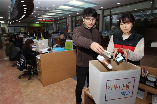 동작구청 민원봉사과에 설치된 기부나눔 박스에 직원들이 생필품을 기부하고 있다.