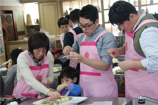티브로드 신입직원들이 28일 한국전통음식연구소 산하 떡 박물관에서 다문화가족 어머니와 아이들과 함께 삼색 쌀엿강정을 만드는 중이다.