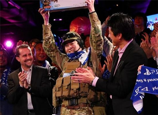 추첨으로 첫 PS4 를 획득한 네코미 씨(가운데)와 앤드류 하우스 소니컴퓨터엔터테이먼트(SCE) 사장(왼쪽)