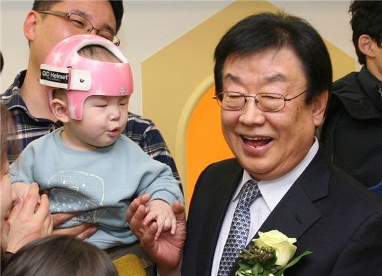 김정남 동부화재 사장(오른쪽)이 22일 '프로미 아이사랑 어린이집' 개원식에 참석해 어린이들과 함께 기념촬영을 하고 있다.