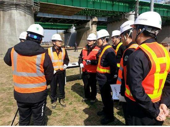조노영(오른쪽에서 4번째, 안경 낀 사람) 코레일 안전본부장이 한강철교 아래서 보강공사 현황설명을 듣고 있다.
