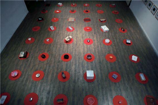 이원호, 'Story I'(스토리 원), 흥정을 통해 부랑자들로부터 구입한 적선 받은 돈과 적선 도구, 빨간 펠트, 프린트, 빨간 스티커, 가변 설치, 2013년.