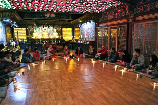 ▲외환은행과 한국불교문화사업단이 지난 22일부터 1박2일간 서울 종로구 금선사에서 실시한 '템플스테이 행사'에 참석한 국내 체류 외국인 고객들이 한국의 불교와 전통문화를 이해하고 소통하기 위해 '촛불 명상 시간'을 체험하고 있다.